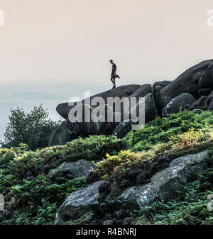 Man standing high up on rocks at the popular destination of The Roaches in North Staffordshire nr the market town of  Leek ,England UK. - Stock Photo