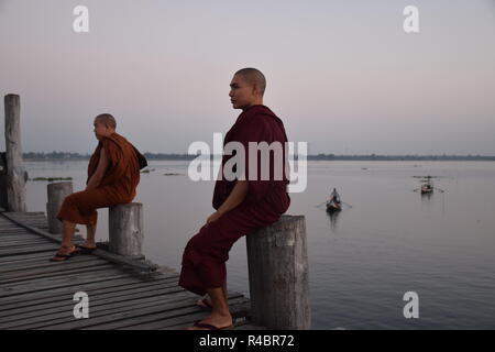 Buddhist monks on U-Bein bridge at sunset in Amarapura, Myanmar - Stock Photo