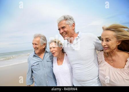 Senior people walking on the beach - Stock Photo