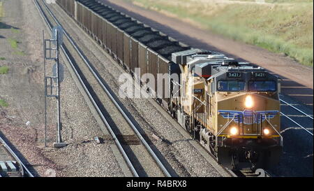 Locomotive and long coal train transporting coal in the Powder River Basin of Wyoming, USA. - Stock Photo