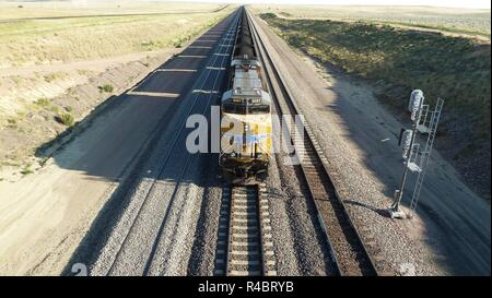 Locomotive and long coal train transporting coal in the Powder River Basin of Wyoming / USA. - Stock Photo