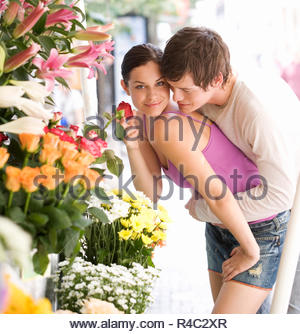 A young couple looking at a flower stall - Stock Photo