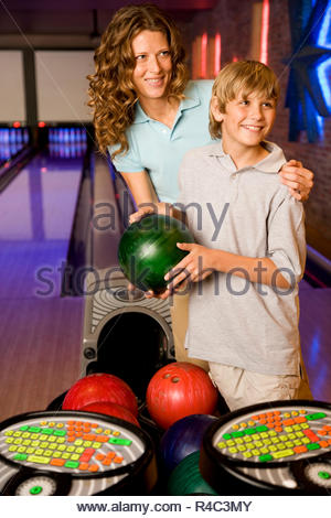 Mother and son in a bowling alley, holding green bowling ball - Stock Photo