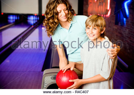 Mother and son in a bowling alley, holding red bowling ball - Stock Photo
