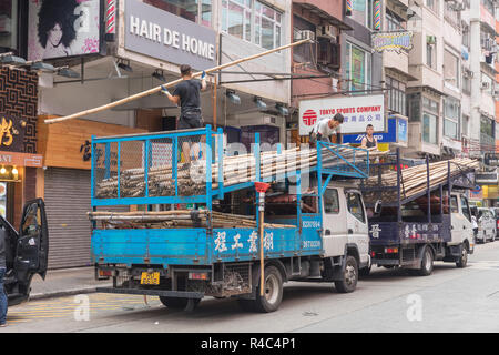 KOWLOON, HONG KONG - APRIL 21, 2017: Workers Unloading Trucks With Bamboo Scaffoldings at Construction Site at Mong Kok in Kowloon, Hong Kong. - Stock Photo
