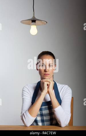 woman in an apron at a table - Stock Photo