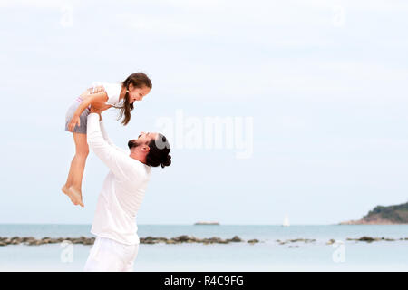 Father and daughter walking on deserted tropical beach together happy loving vacation - Stock Photo