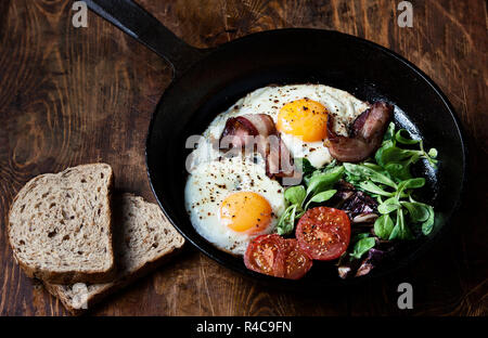 Breakfast set. Pan of fried eggs with bacon, tomato on wooden background - Stock Photo