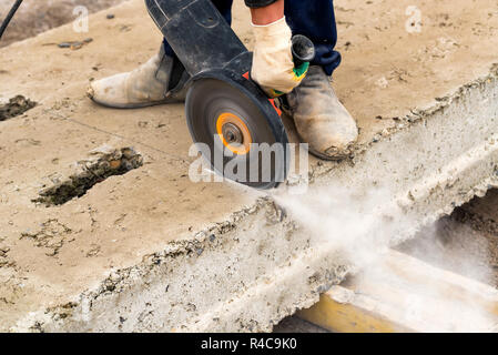 Close up worker cuts concrete with circular saw - Stock Photo