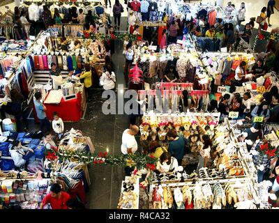 QUEZON CITY, PHILIPPINES - NOVEMBER 18, 2018: Customers of a mall bazaar choose from a variety of products from bazaar stalls. - Stock Photo