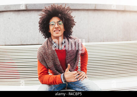 Young handsome curly guy showing thumbs up. Happy foreign student smiling and happy with life positive emotion - Stock Photo
