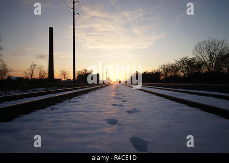 Footprints in the snow between railroad tracks at golden hour on the east coast - Stock Photo