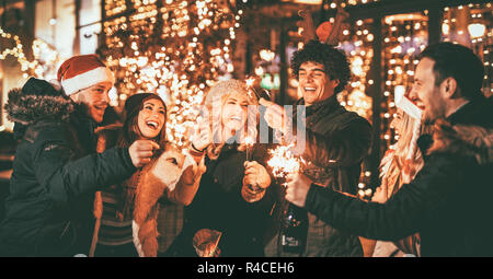 Three couple with sparklers enjoying Christmas outdoor party in the city street at night and with a lot of lights on background. - Stock Photo