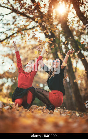 Beautiful young  mother and her happy daughter having fun in the forest in the sunset. They are crouching and having fun with fallen leaves. - Stock Photo