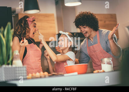 Happy parents and their daughter are preparing cookies together in the kitchen. Little girl is making fun putting some dough to mer mother nose. - Stock Photo