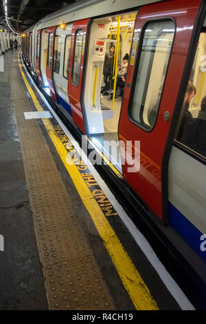 Tube station in London, 'Mind the Gap' painted on the platform - Stock Photo