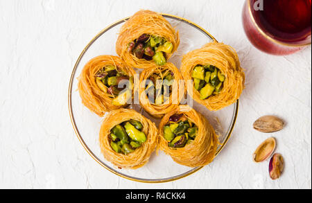 Arabic dessert with pistachio on a plate top view - Stock Photo
