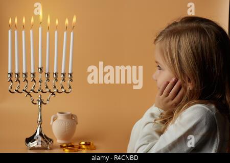 Charming girl looking at burning menorah candles - Stock Photo