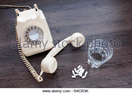 Old fashioned telephone with receiver off the hook and a glass of water with tablets - Stock Photo