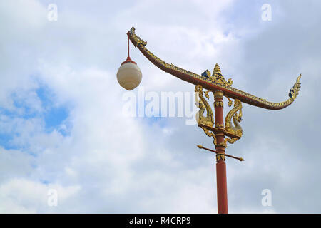 Thai Vintage Racing Boat Shaped Street Lamp against Cloudy Sky of Nan Province, Northern Region, Thailand - Stock Photo