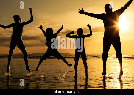 Father and children playing on the beach at the sunset time. - Stock Photo