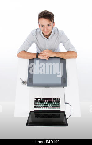 Graphic designer seen from above with tablet and laptop, he is smiling and with his arms resting at the desk - Stock Photo