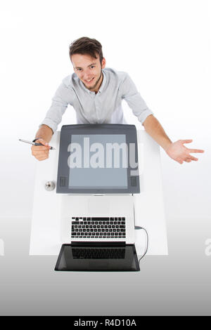 Graphic designer seen from above with tablet and laptop, he is smiling and with open arms holding a graphic pen in one hand - Stock Photo