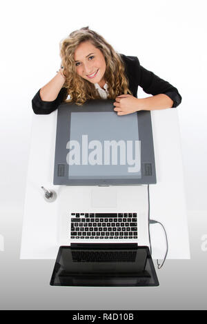 Graphic designer seen from above with a tablet and a laptop, she is smiling and with her arms resting on the desk and her head - Stock Photo