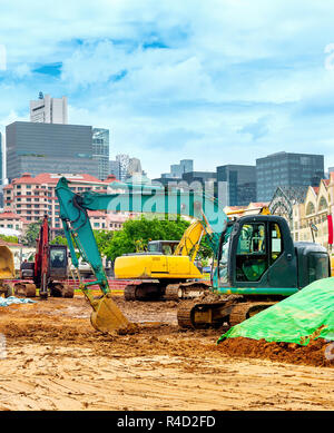 Excavators at construction site in Singapore downtown, modern city skyline on background - Stock Photo