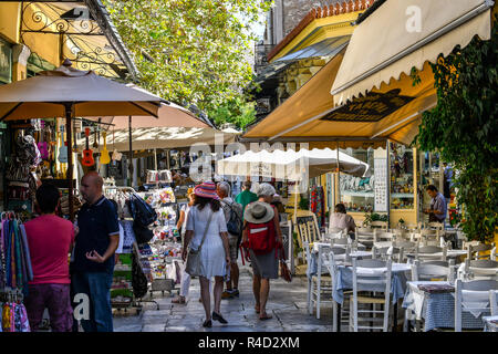 Tourists walk the narrow path between souvenir shops and outdoor sidewalk cafes in the touristis Plaka section of Athens, Greece. - Stock Photo
