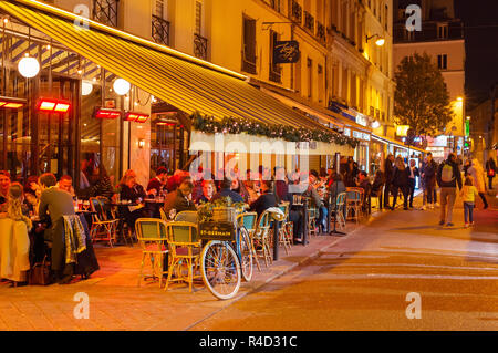 PARIS, FRANCE - NOVEMBER 09, 2018: People at a street restaurant in Paris at night. Paris is the most visited city in Europe - Stock Photo