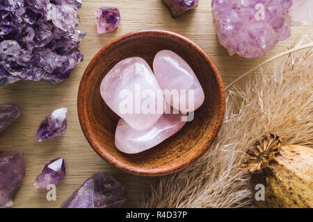 Teak Bowl of Rose Quartz with Amethyst Crystals and Dried Poppy Flower on Wood Table - Stock Photo