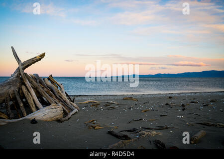 Sunset hues over horizon with driftwood shelter on  Collingwood beach in South Island New Zealand - Stock Photo