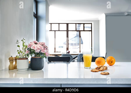 Appetizing sweet orange juice and one drinking glasses standing on a white table in the kitchen for a breakfast. - Stock Photo