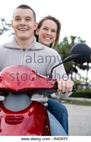 A young couple on a scooter - Stock Photo
