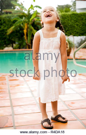 little Hispanic girl laughing standing by pool - Stock Photo