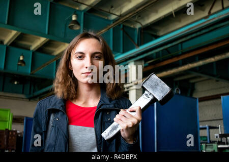 Belarus, Zhodino forge plant for heavy stampings 12.10.2018: A young girl with a hammer in the workshop of a blacksmith factory on the background of i - Stock Photo
