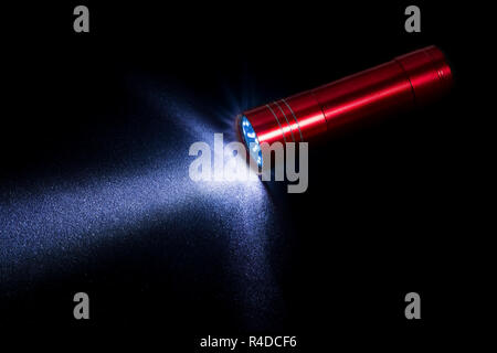 A small red lantern shines on a black background. - Stock Photo