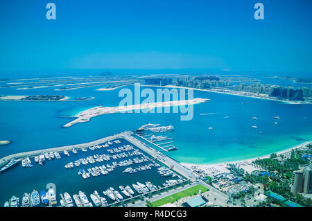 Aerial view of Palm Jumeirah Island with luxury yachts in the front. Development of Dubai. - Stock Photo