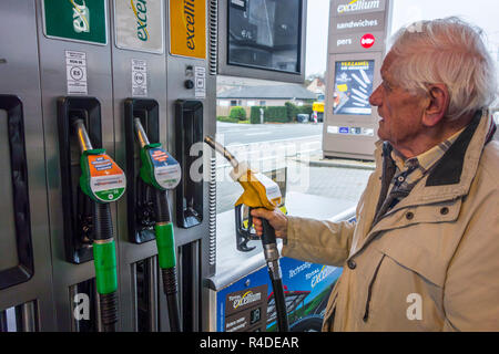 Elderly man selecting diesel fuel pump nozzle and watching expensive price at fuel dispenser of gas station for refueling his car in Belgium, Europe - Stock Photo
