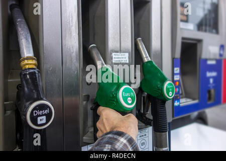 Man selecting petrol fuel pump nozzle at gas station for refueling his car in Europe - Stock Photo