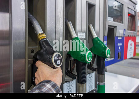 Man selecting diesel fuel pump nozzle at gas station for refueling his car in Europe - Stock Photo