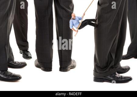 Businessman climbing another's leg - Stock Photo