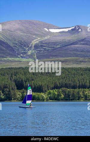 Sailing boat on Loch Morlich in front of the Cairngorm Mountains, Cairngorms National Park, Badenoch and Strathspey, Highland, Scotland, UK - Stock Photo