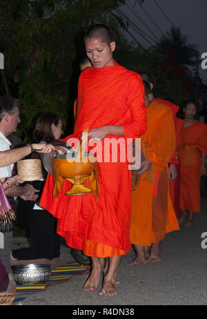 Starting before daybreak orange-robed Laos Buddhist monks take alms from the devoted every day in early morning - Luang Prabang, Northern  Laos. - Stock Photo
