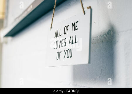 Wooden board with text all of me loves all of you, love sign on the wall home interior modern - Stock Photo