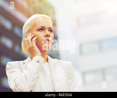 serious businesswoman with smartphone outdoors - Stock Photo
