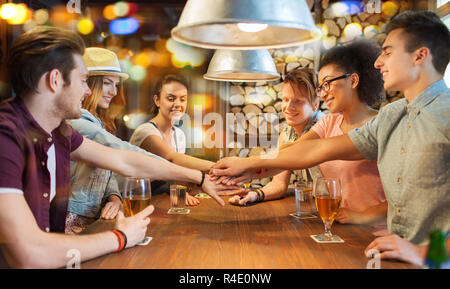 happy friends with drinks and hands on top at bar - Stock Photo