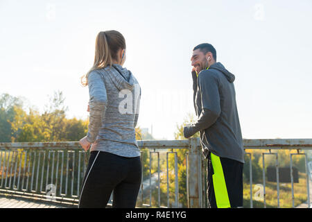 happy couple with earphones running outdoors - Stock Photo