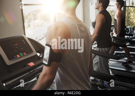 smiling men exercising on treadmill in gym - Stock Photo